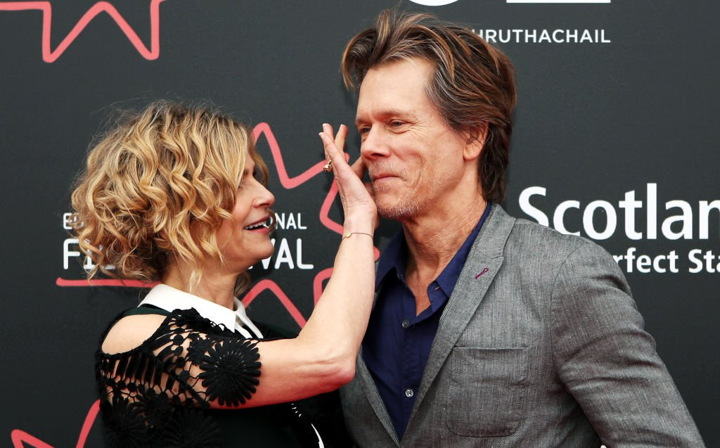 Kevin Bacon's wife and director Kyra Sedgwick wipes something off his face as they attend the Story of a Girl world premiere on June 22, 2017 | Photo: Getty Images