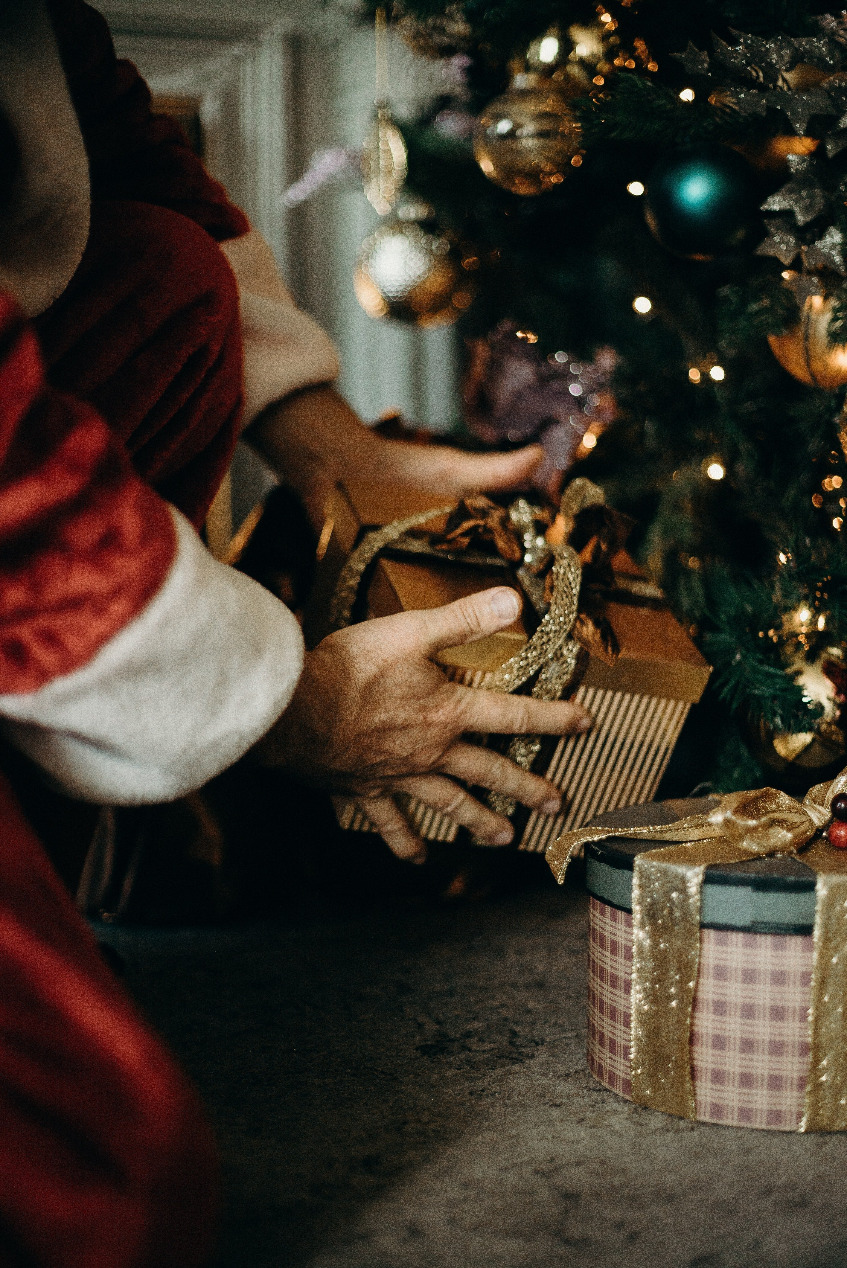 Santa secretly putting a gift under the Christmas tree. | Source: Pexels.