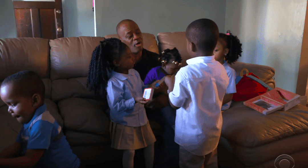 Lamont Thomas and his children on the sofa in the living room of their home. | Photo: YouTube/CBS Evening News