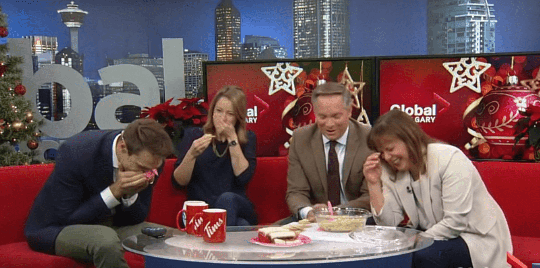 Global News Calgary anchor Leslie Horton sharing her favorite treat with co-anchors Scott Fee, Jordan Witzel and Amber Schinkel. | Photo: YouTube/Global News