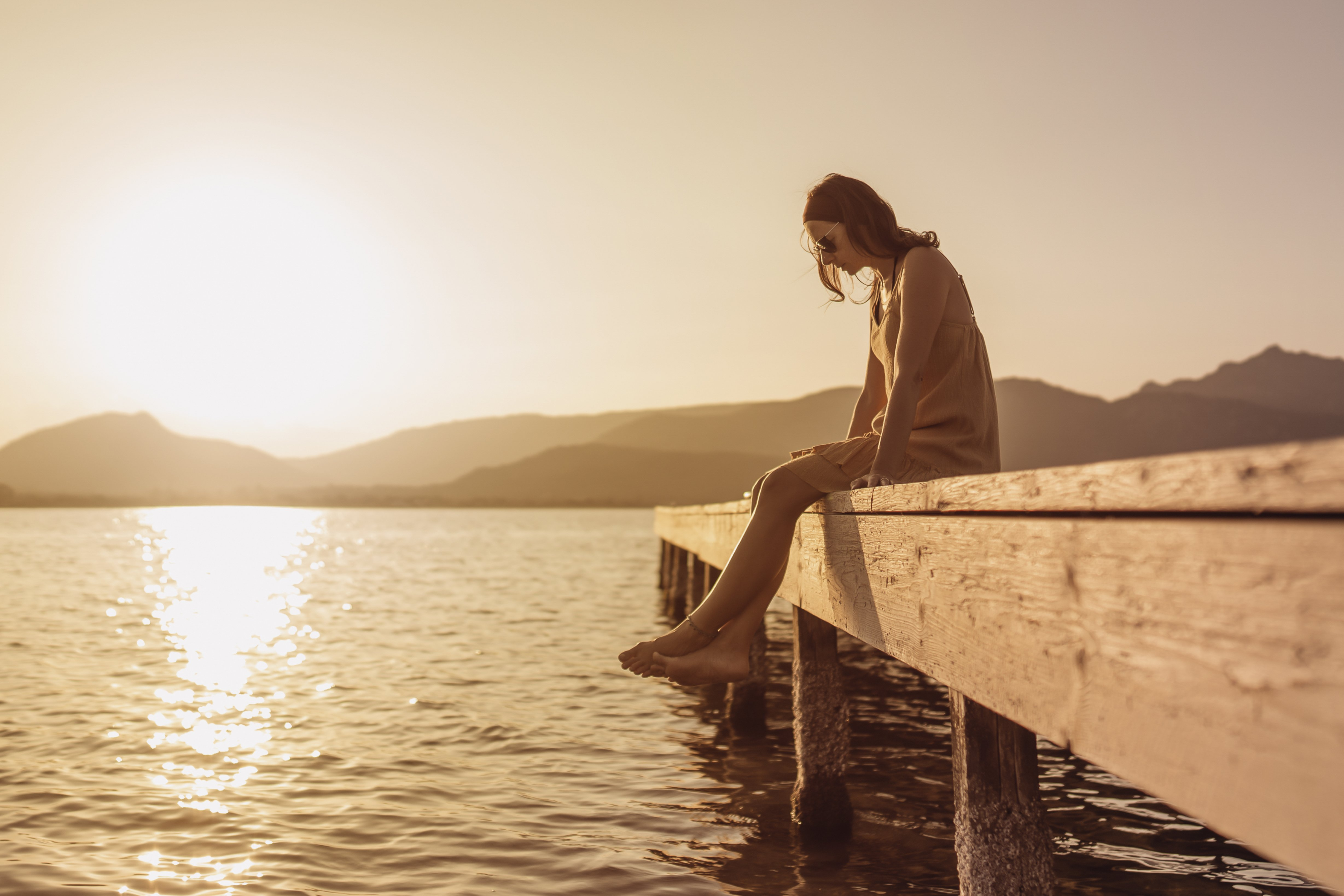 A young woman sitting on a pier at sunset.│ Source: Shutterstock
