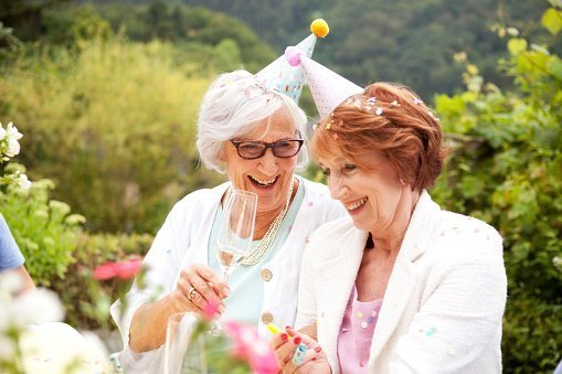 Two elderly woman pictured drinking champagne at birthday party | Photo: Getty Images