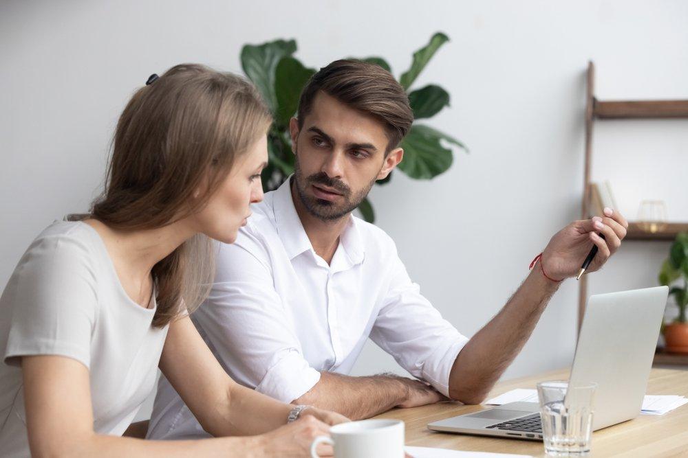 Compañeros de trabajo sentados en el escritorio de la oficina mientras discuten proyectos e intercambian diferentes opiniones. | Fuente: Shutterstock