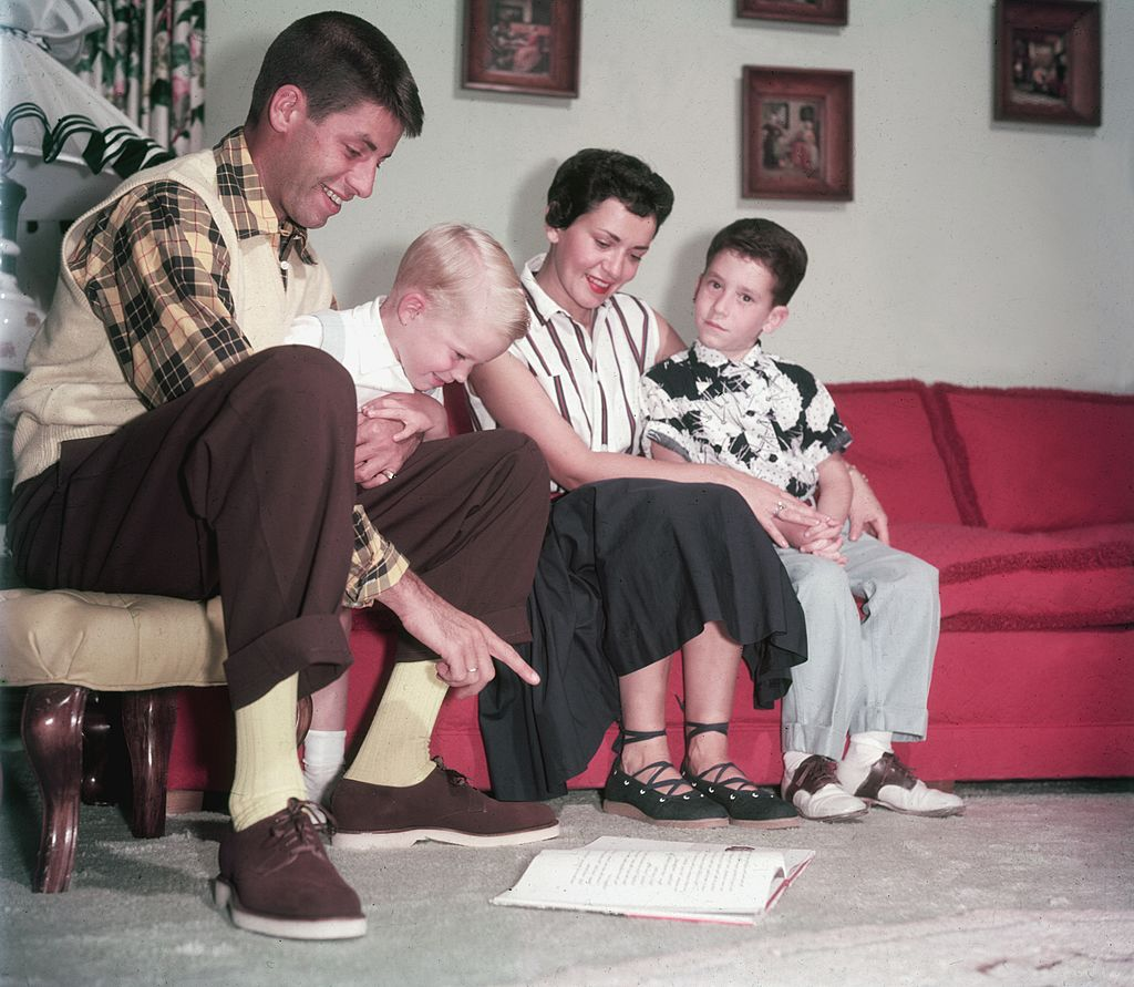 American actor and comedian Jerry Lewis sitting on a couch with wife, Patti Palmer, and their two sons, Gary and Ronald circa 1960   Photo: Getty Images