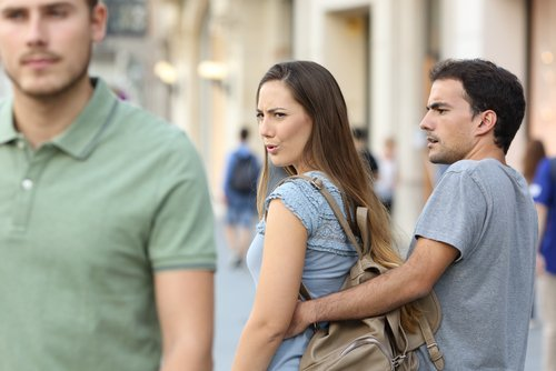 A woman in a relationship looking at another man. | Source: Shutterstock.