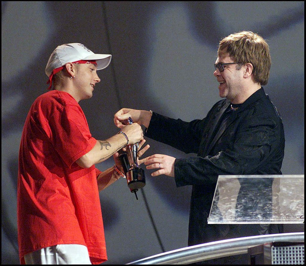 American rap star Eminem accepts an award from British musician Sir Elton John on stage at the 2001 Brit Awards held at Earls Court Exhibition Centre in London | Photo: Getty Images