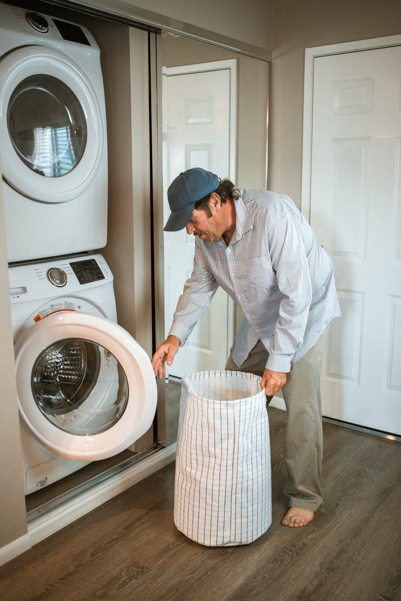 Man putting clothes in the washing machine | Source: Pexels