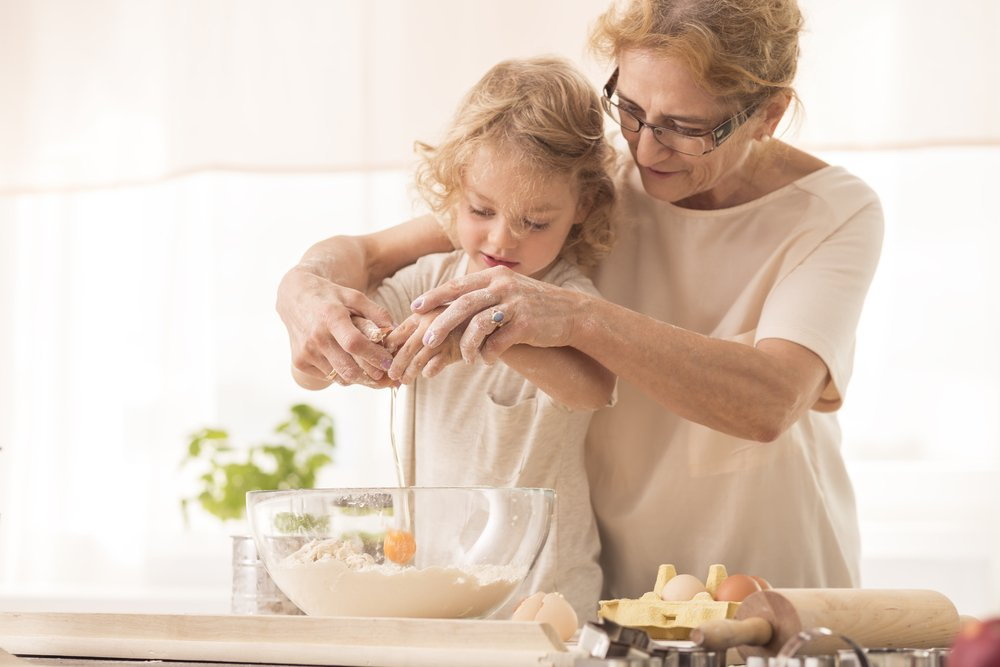 Grandmother helping her granddaughter out in the kitchen | Photo: Shutterstock