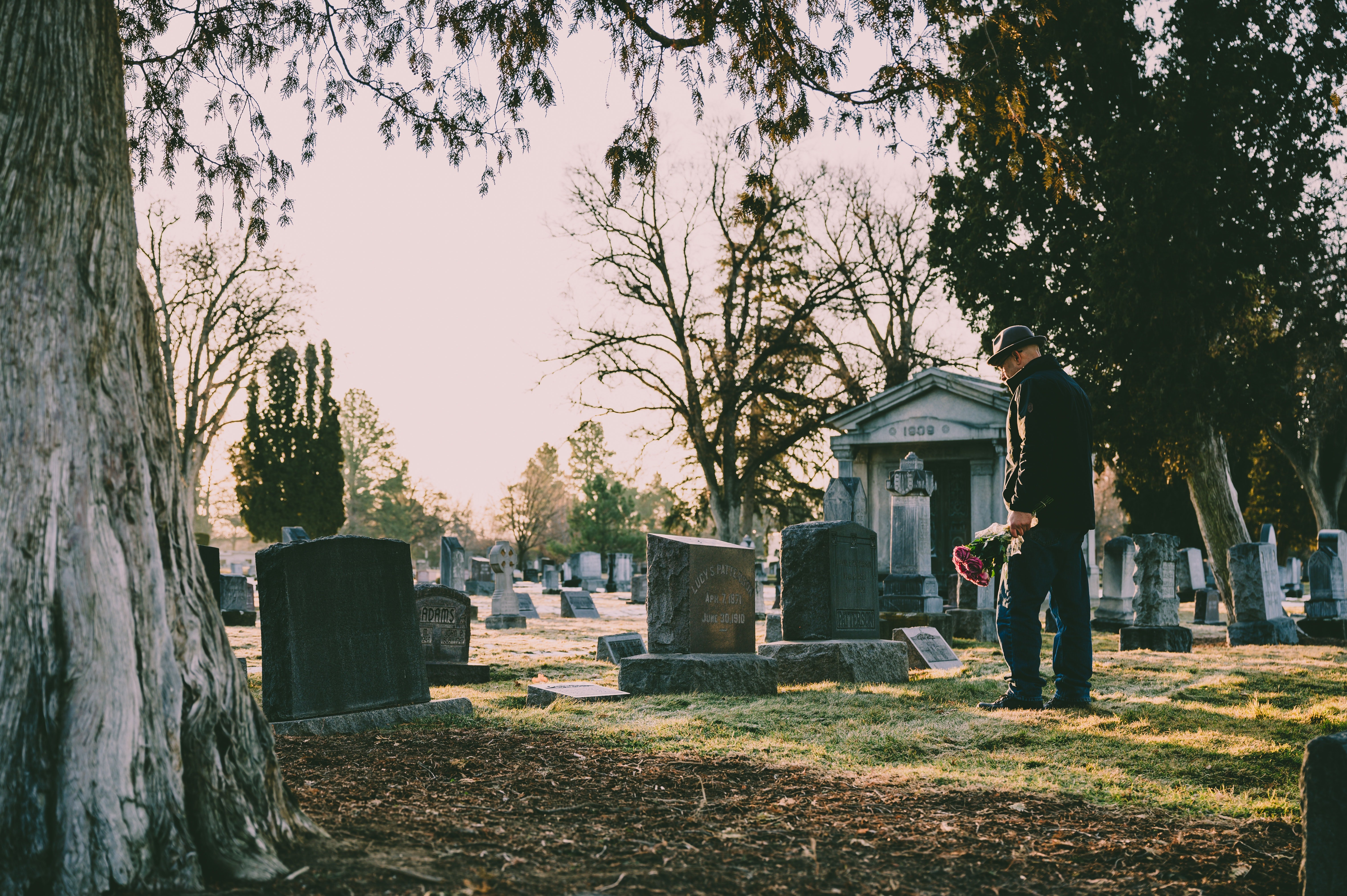 Man standing in a black jacket in front of a grave with flowers in his hand | Photo: Pexels