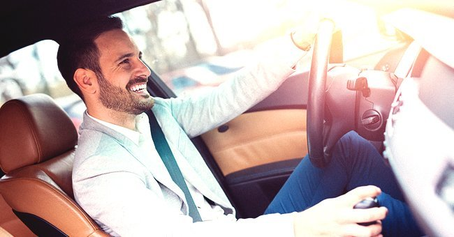 A man driving and laughing in the driver's seat | Shutterstock.com