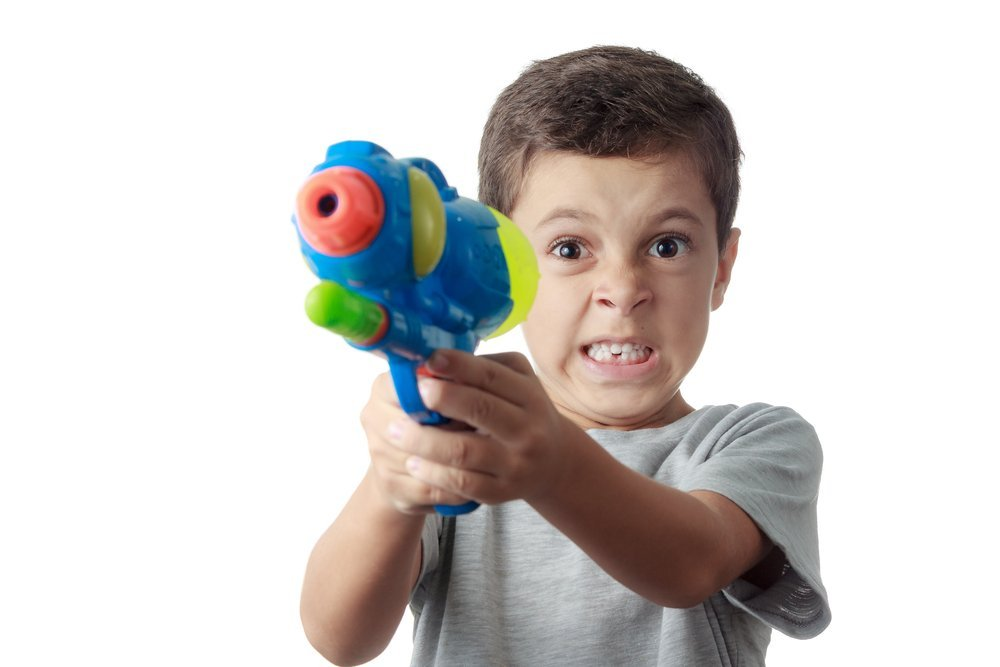 Little boy with funny expression playing with plastic water gun. | Photo: Shutterstock