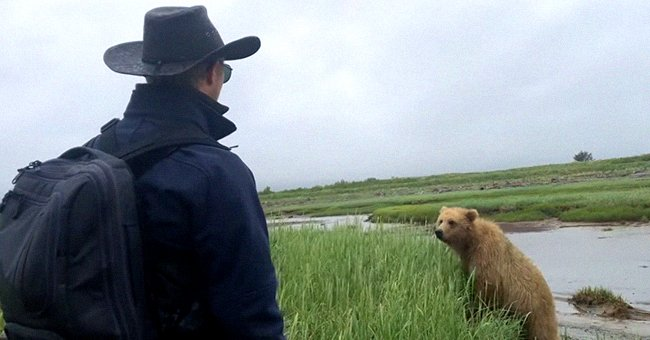 Man tries to scare bear away from him and his group | Photo: Youtube/The Bear Necessities