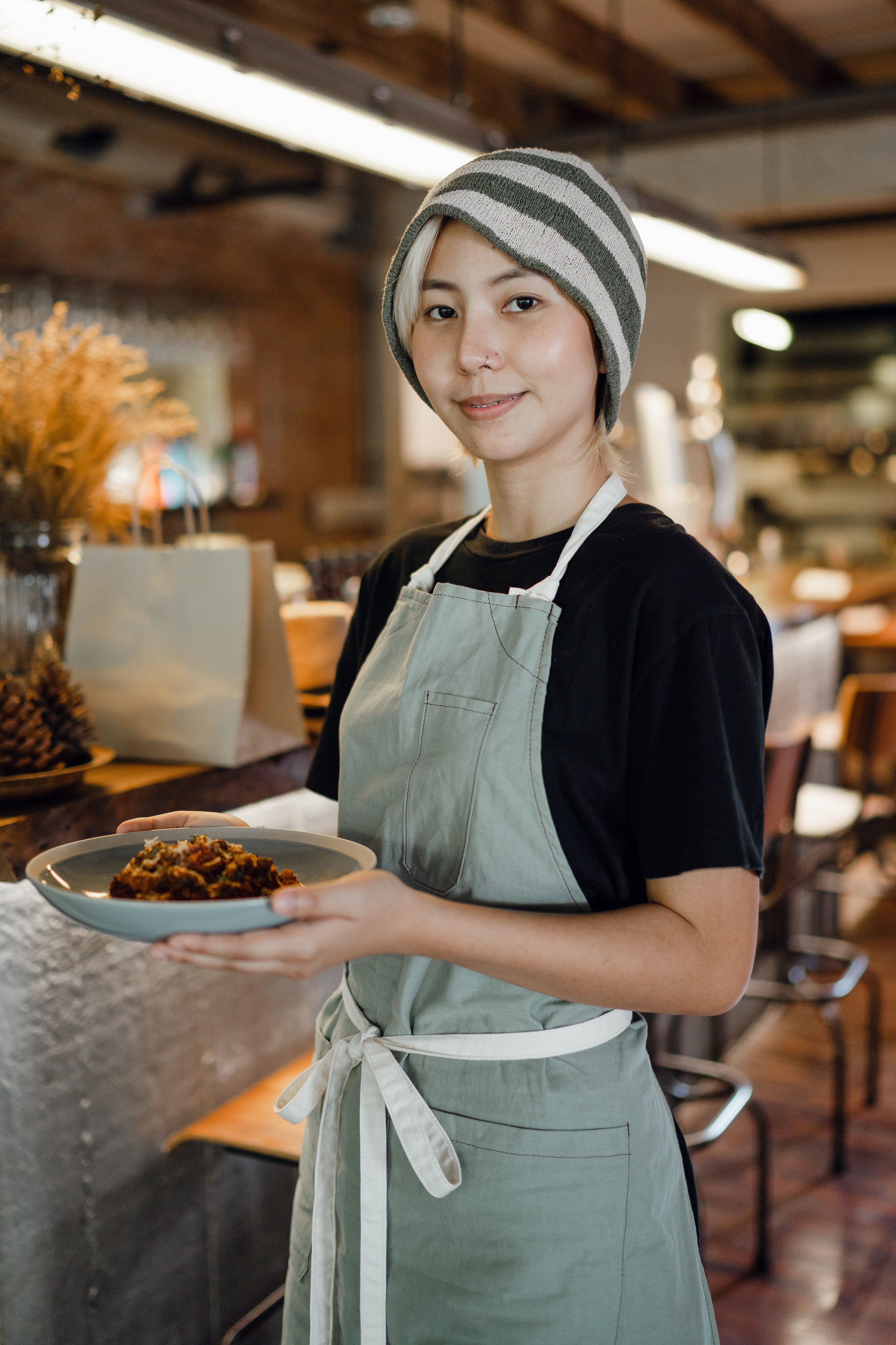 A woman carrying a plate of food in a restaurant.   Photo: Pexels/Ketut Subiyanto