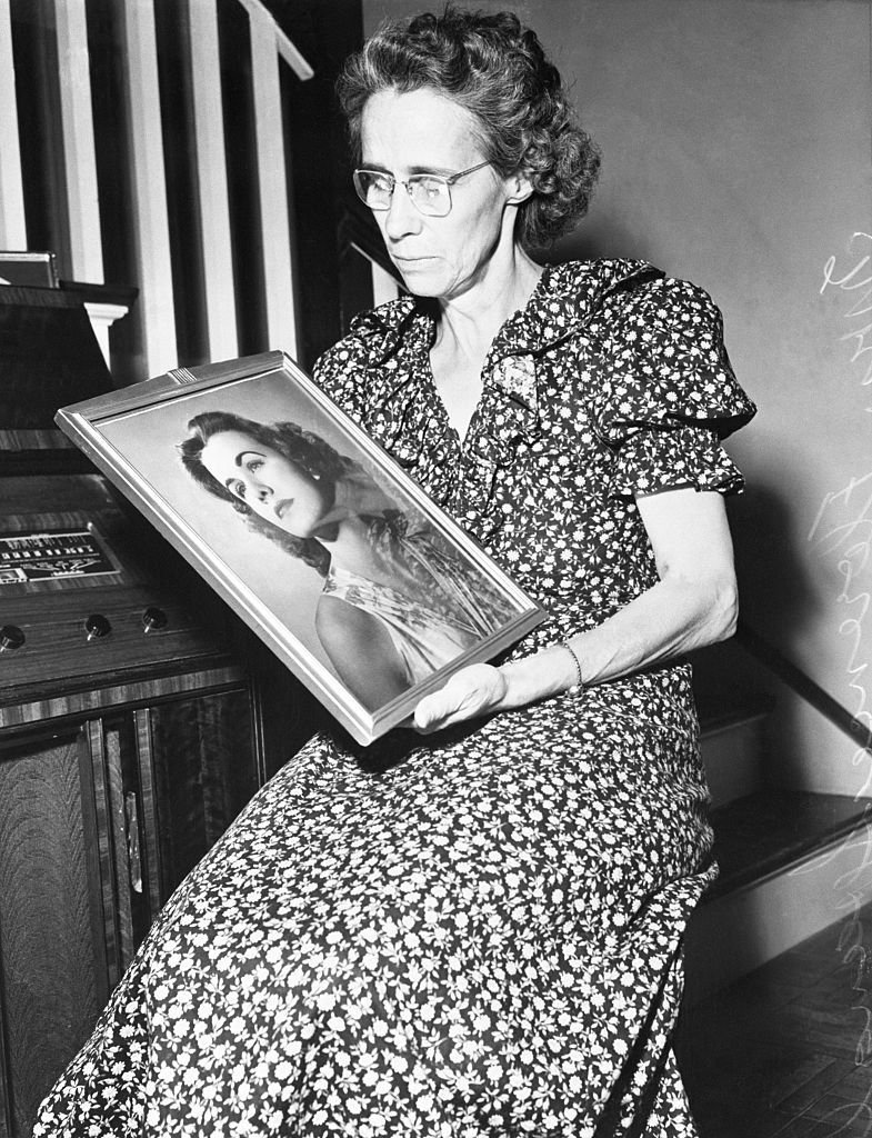 Jean's mother, Florence, listening to the radio while looking at a photograph of her missing daughter, 1949 | Photo: Getty Images