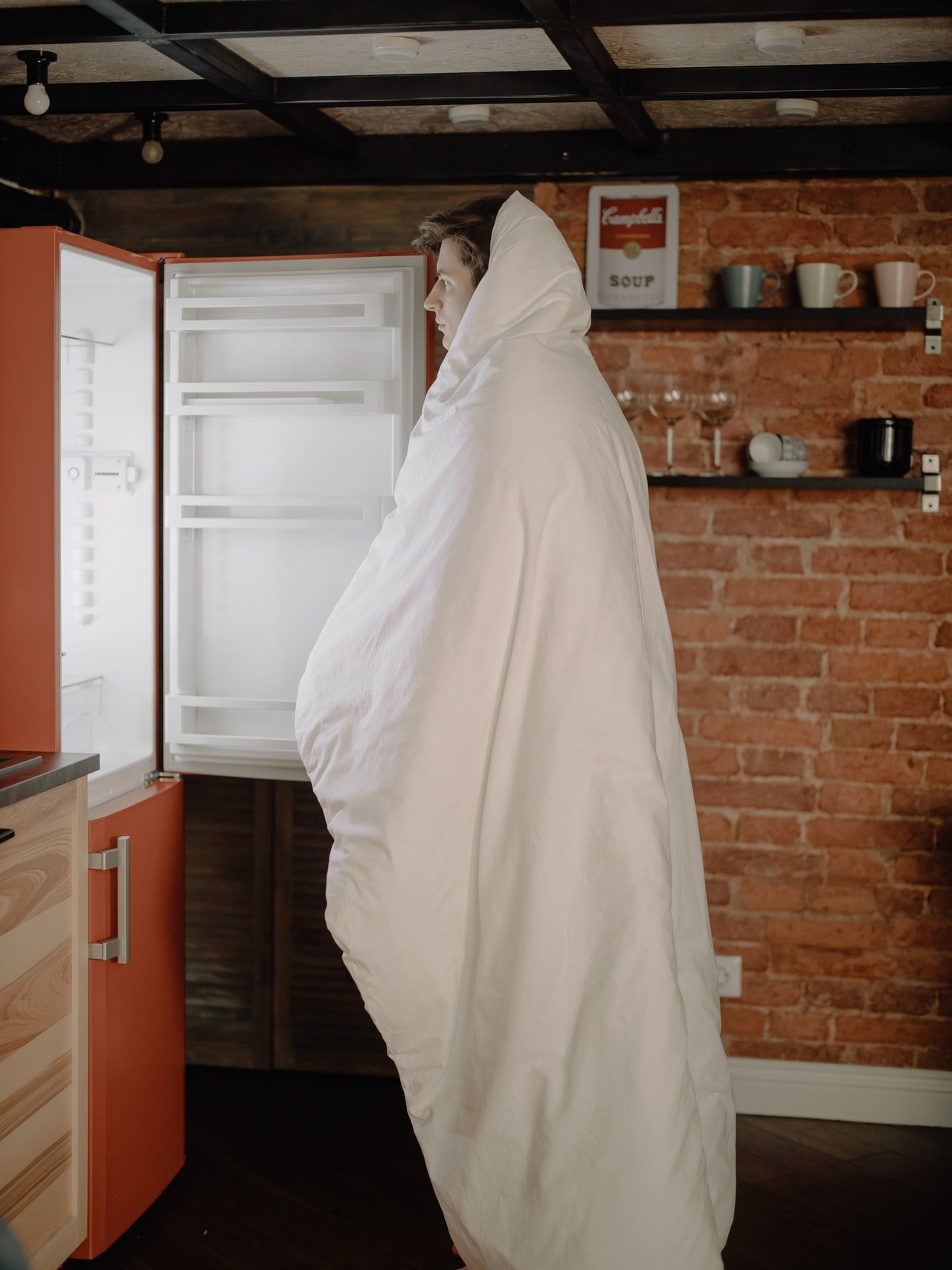Photo of a man standing in front of an open refrigerator | Photo: Pexels