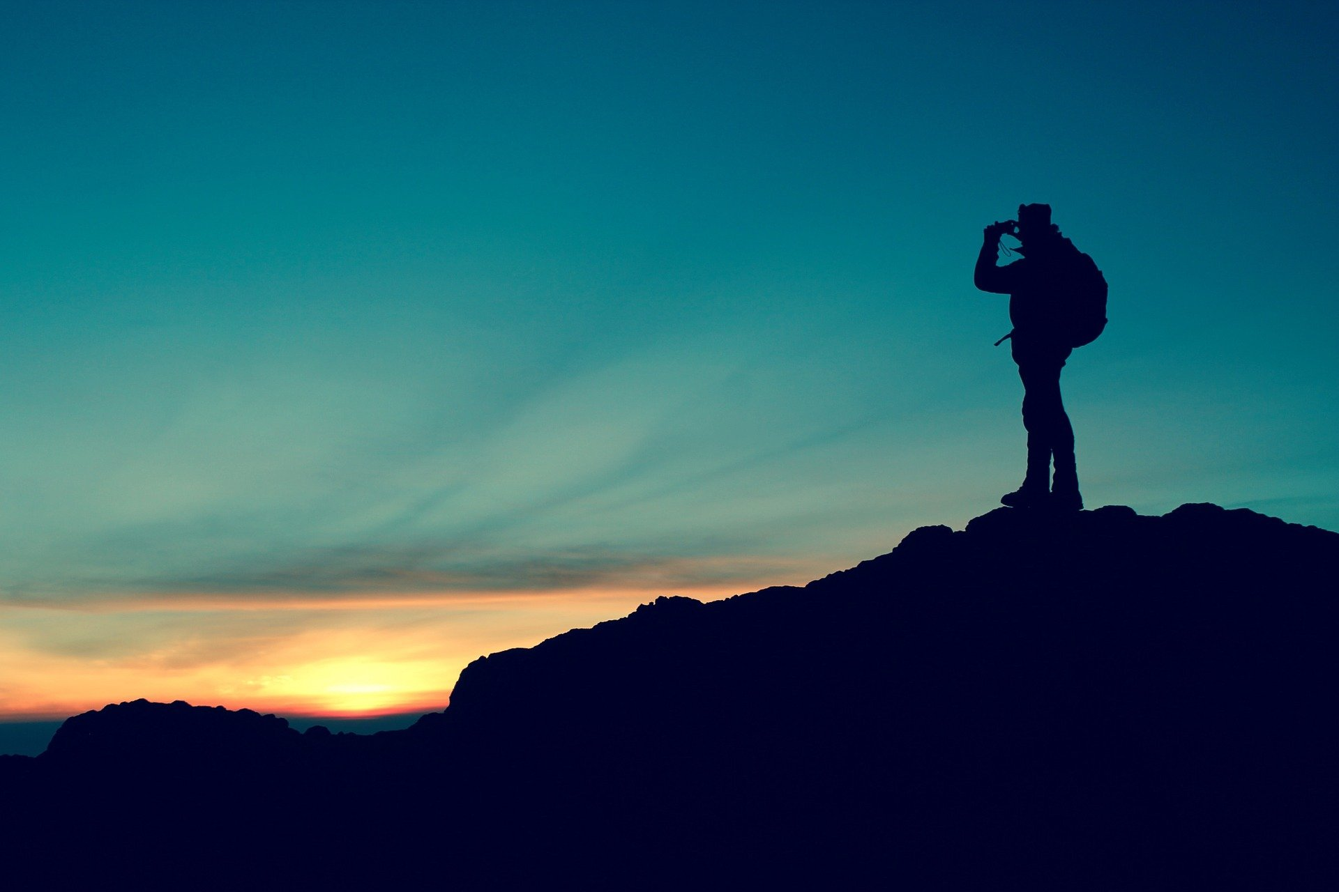 A silhouette of a hiker taking in the views atop a mountain   Photo: Pixabay/Free-Photos