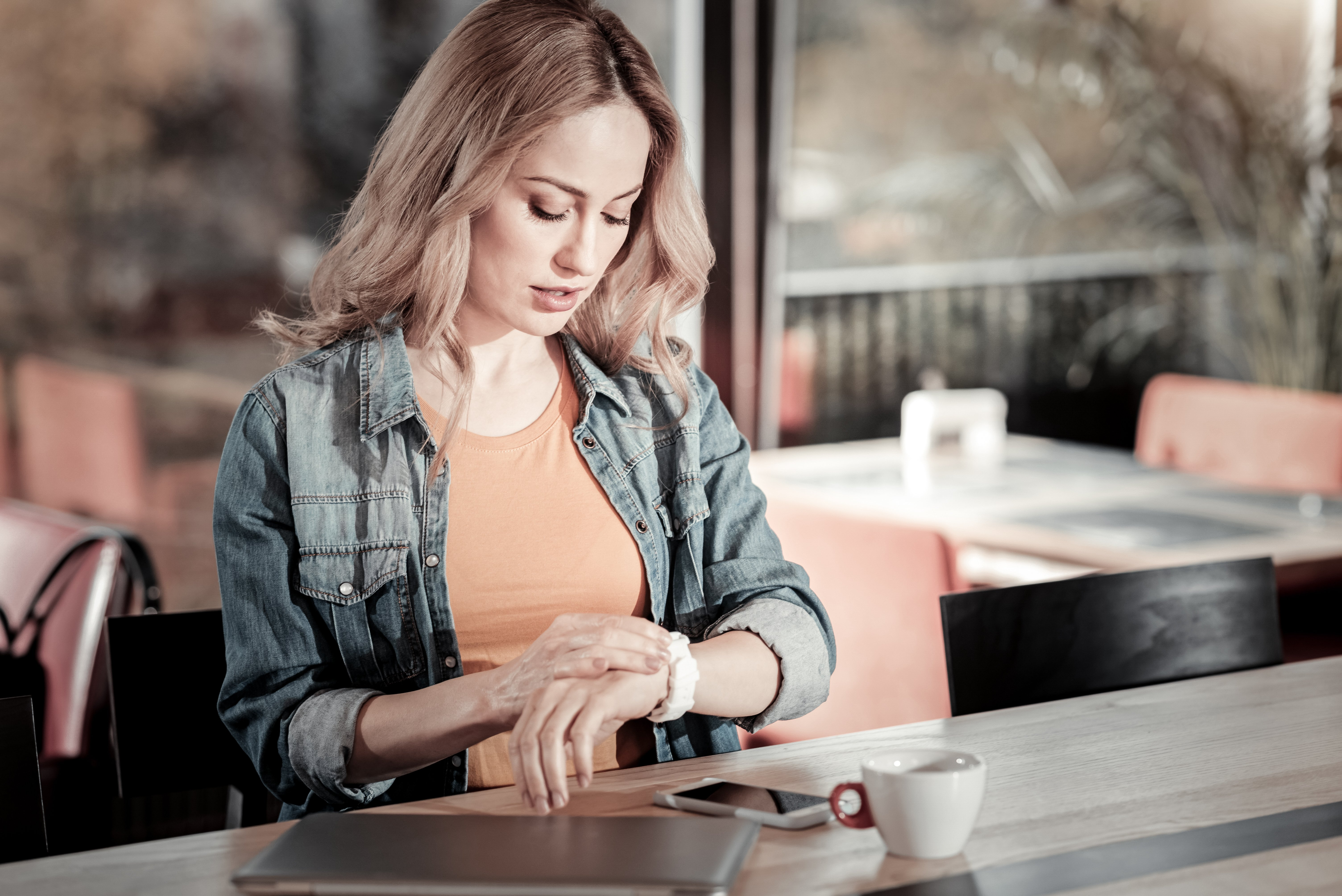 Woman looking at her watch. Image credit: Shutterstock