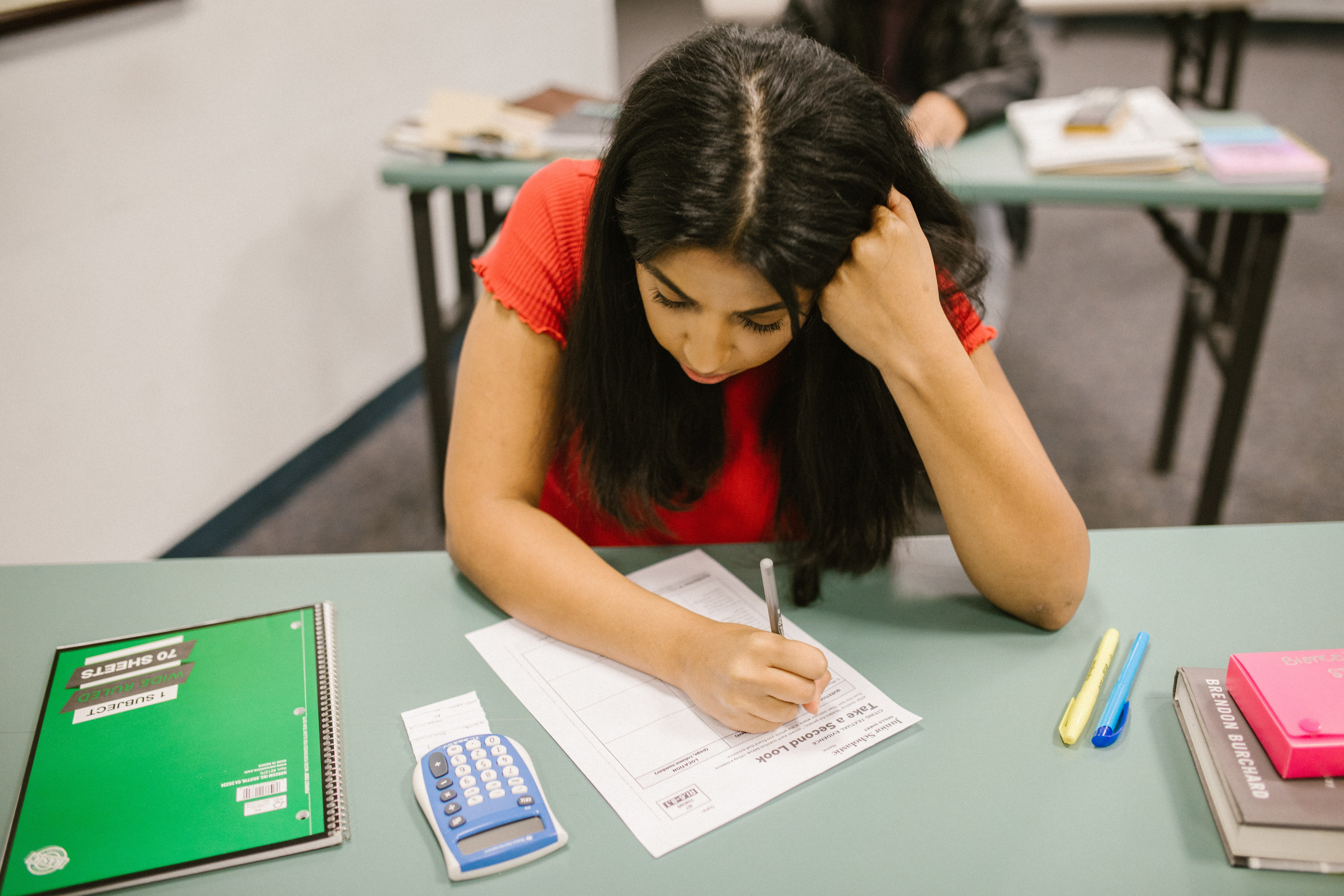 A female student writing a test with a calculater on her desk.   Pexels/ RODNAE Productions