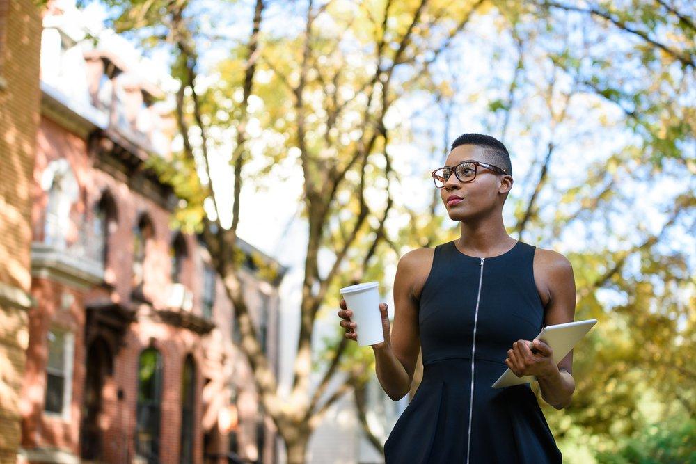 Joven empresaria caminando por la calle. | Fuente: Shutterstock