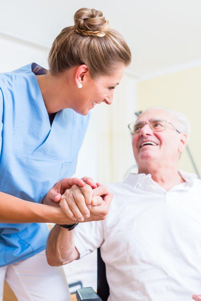 Une infirmière tenant la main d'un homme agé dans une maison de retraite. | Shutterstock