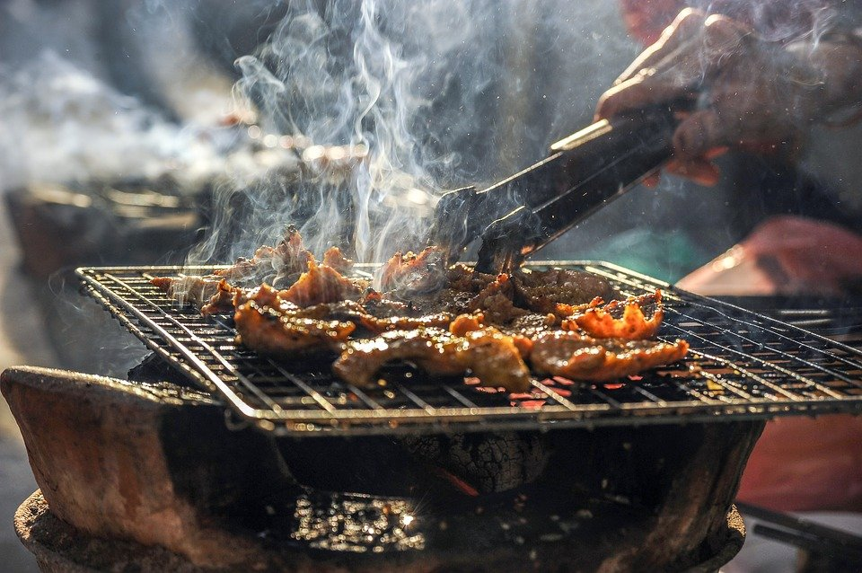 A photo of a man making an outdoor barbecue. | Photo: Pixabay