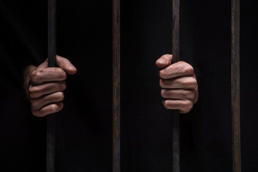Gros plan sur les mains d'un homme derrière les barreaux de prison sur fond noir. | Shutterstock