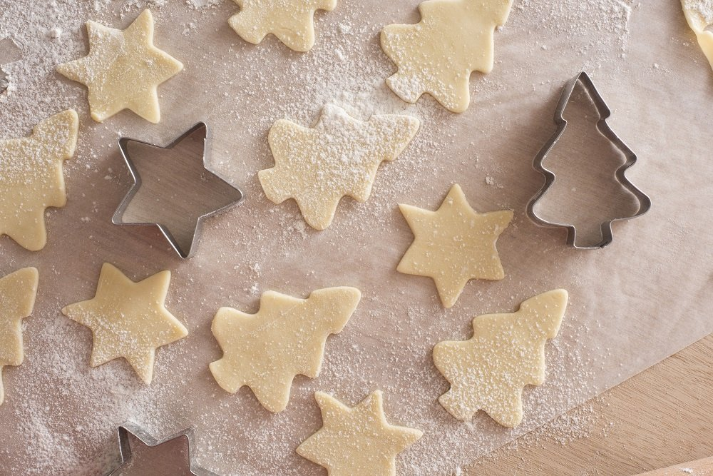 Making Christmas cookies with star and tree-shaped cookie cutters in an overhead view of uncooked pastry shapes on oven paper | Photo: Freeimageslive/christmashat