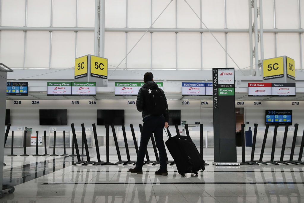 A person in the airport, carrying luggage. | Source: Getty Images