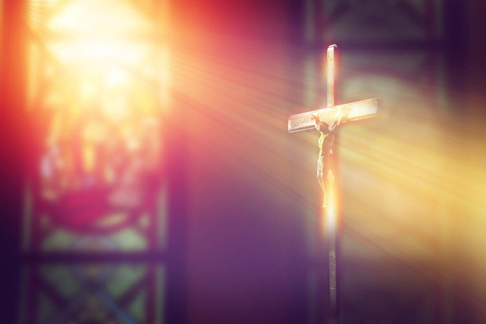 Luz del vitral cayendo sobre la cruz.| Fuente: Shutterstock
