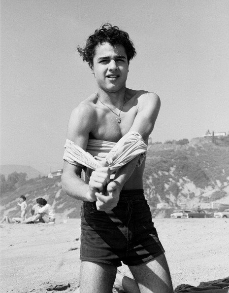 Sal Mineo takes his shirt off on the beach in 1956, in Santa Monica, California. | Source: Getty Images.
