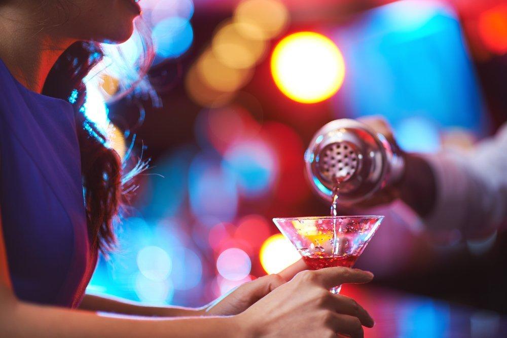 Chica joven sostiene una copa de martini en un bar. | Imagen: Shutterstock