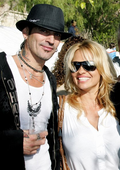 Musician Tommy Lee and actress Pamela Anderson pose at the home of John Paul DeJoria, CEO and co-founder of John Paul Mitchell Haircare Systems, during his annual party to thank movie, television and music star friends and his co-workers for their charitable work on December 24, 2005, in Malibu, California. | Source: Getty Images
