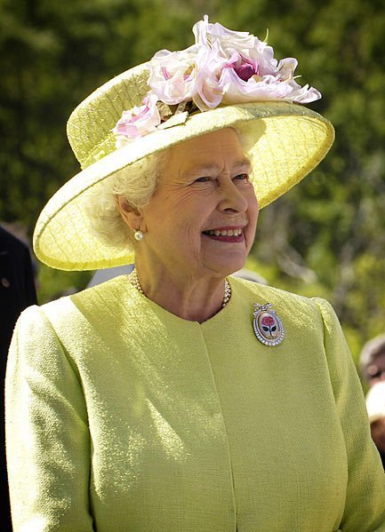 Her Majesty the Queen of the United Kingdom smiling away from the camera during a visit in NASA's Goddard Space Flight Center, Maryland, USA. | Source: WikiMedia Commons