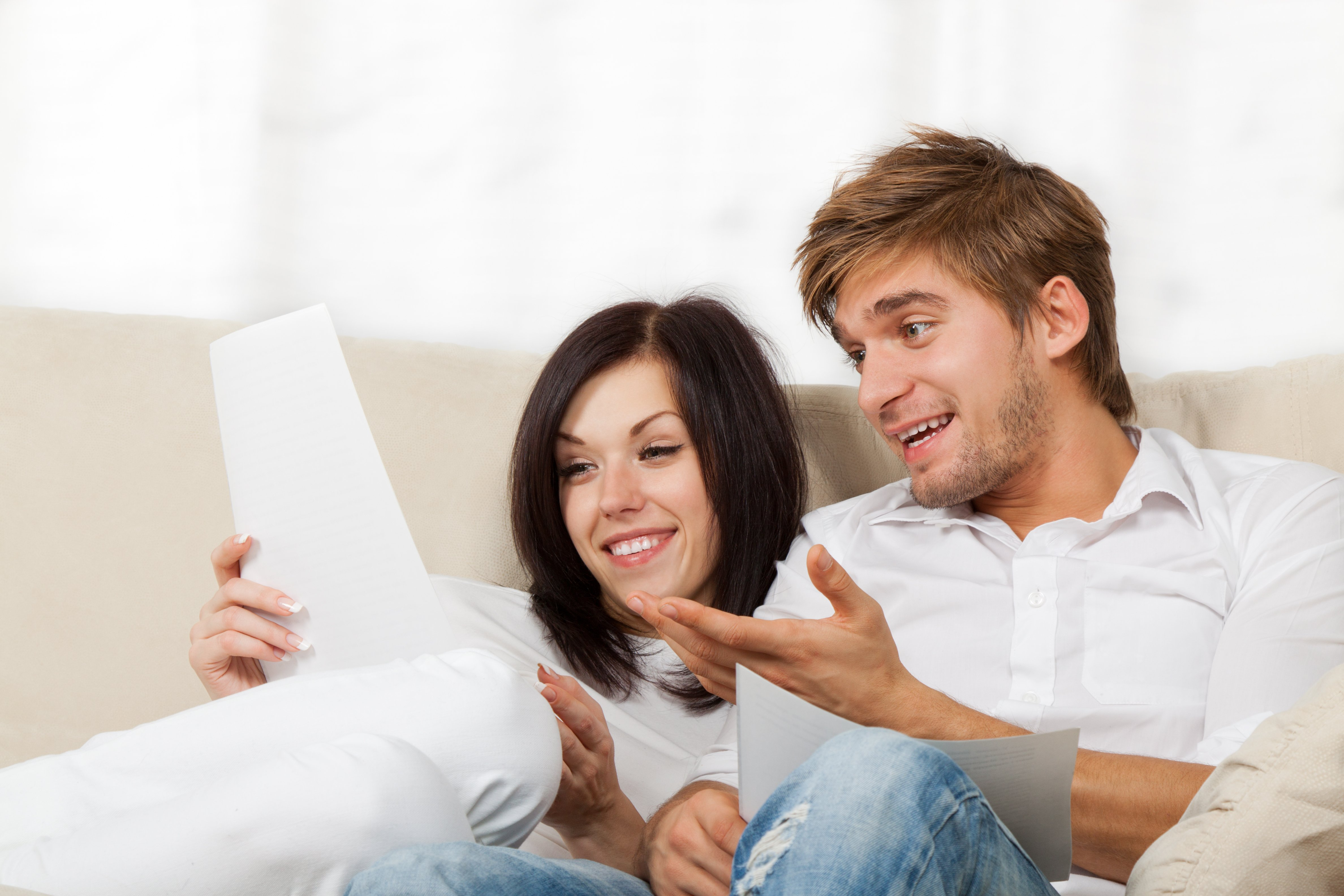 Happy couple reading a letter in their living room, young smile man and woman sitting on couch | Photo: Shutterstock.com