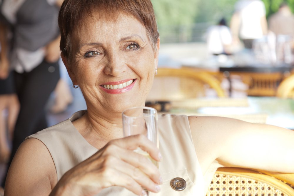 A senior woman with a glass of drink. | Photo: Shutterstock