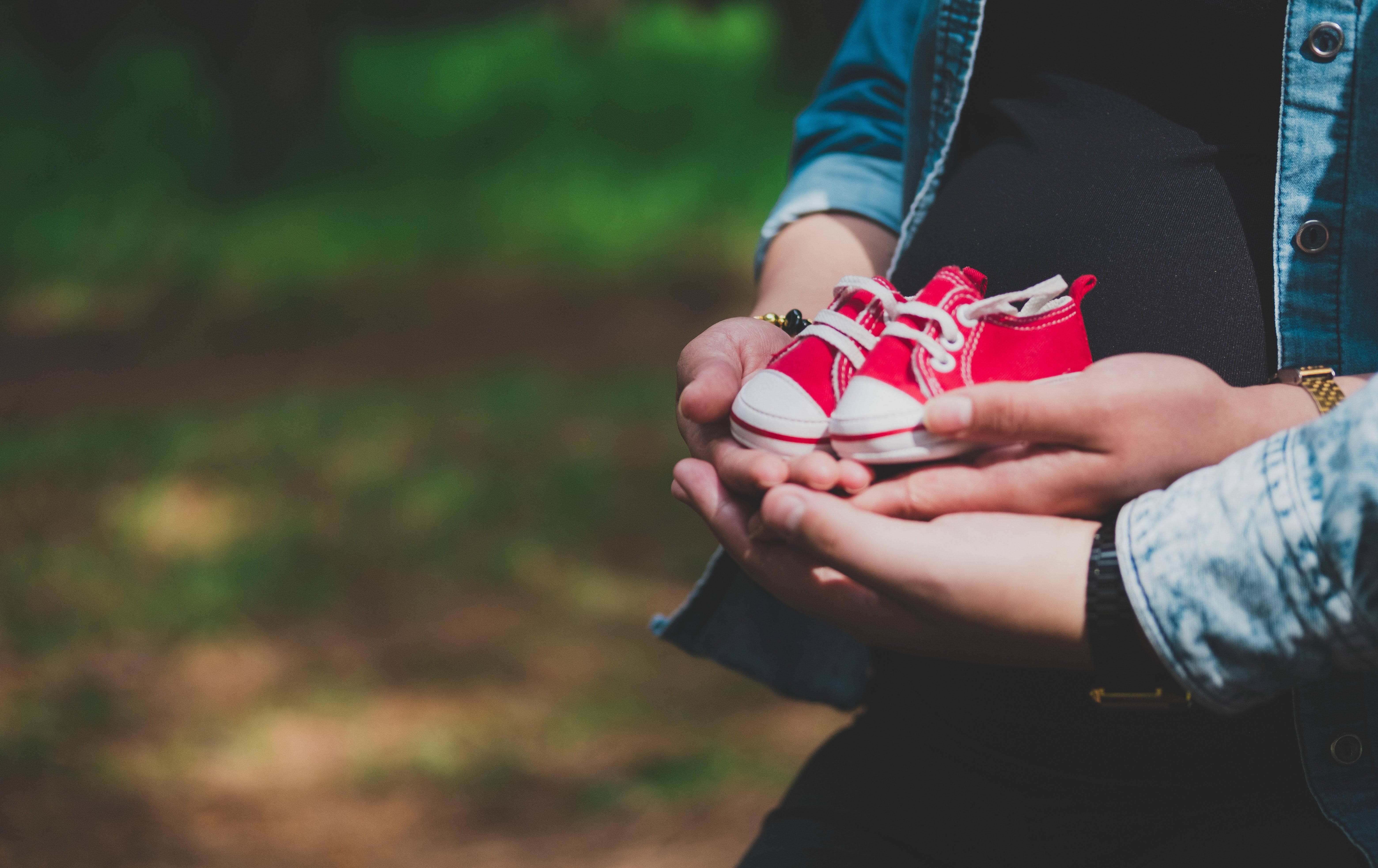 Couple hold a pair of tiny baby shoes | Photo: Unsplash/frankcreative360