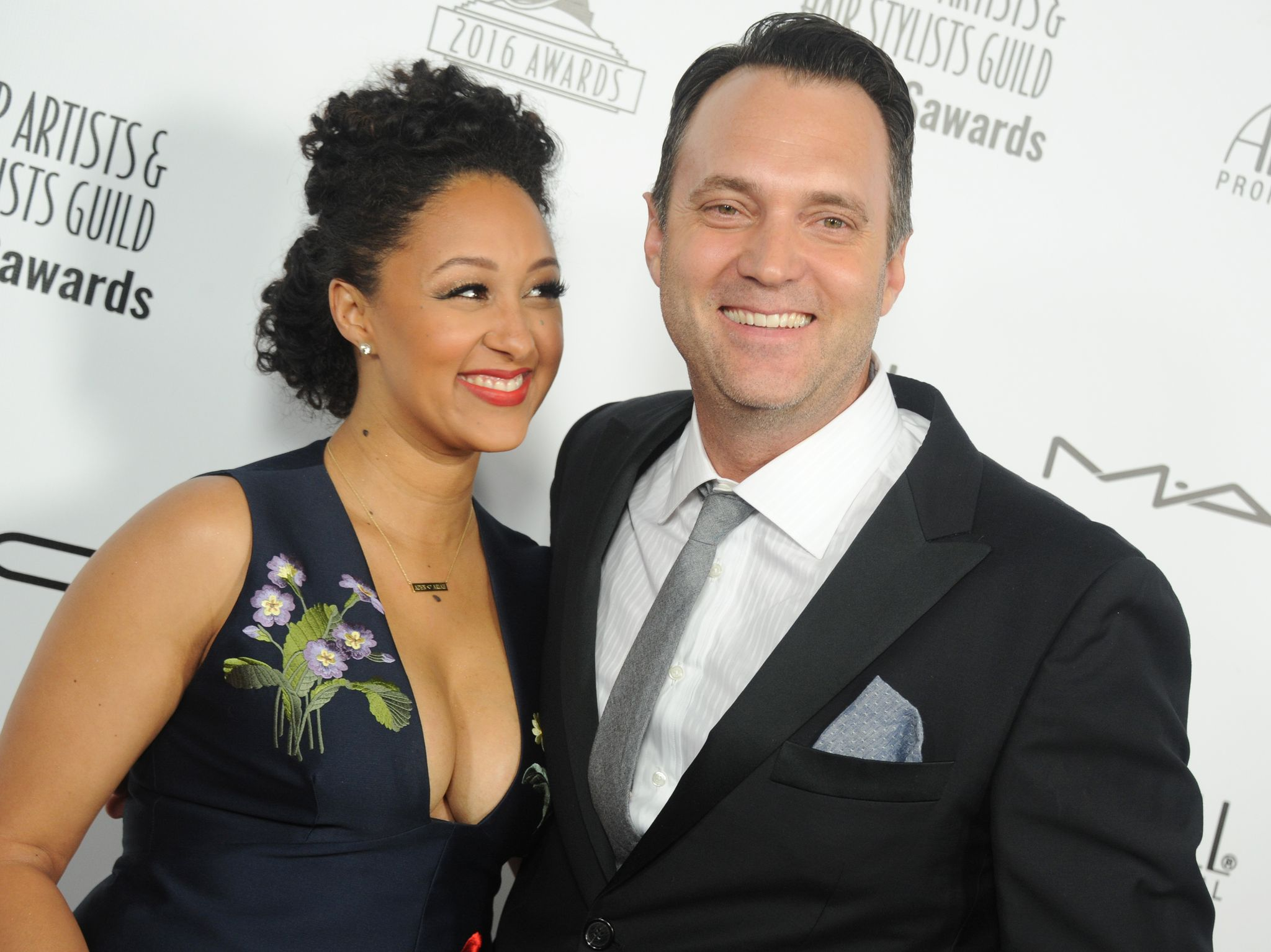 "Tamera Mowry-Housley and Adam Housley arrive on the red carpet of the ""Make-Up Artists and Hair Stylists Guild Awards"" on February 20, 2016, in Hollywood, California 