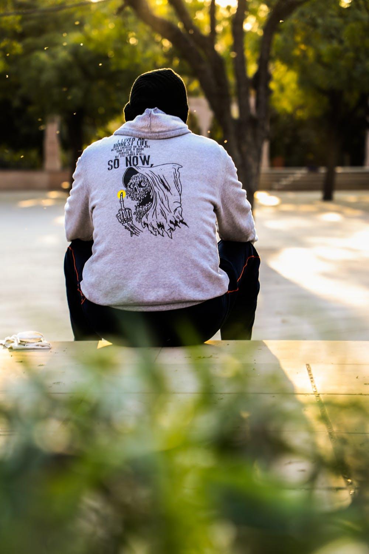 Hombre sentado en acera. | Foto: Pexels
