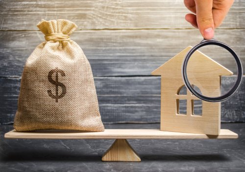 A scaled money bag and wooden house. | Photo: Shutterstock.