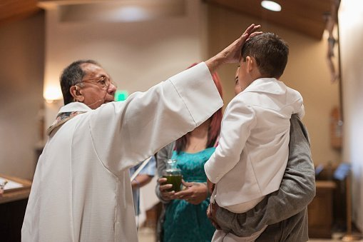 Priest pictured anointing a boy in church | Photo: Getty Images