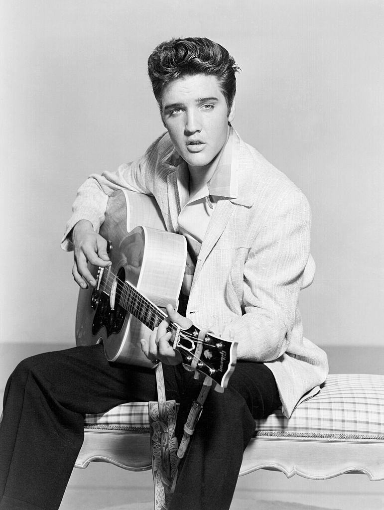 Elvis Presley strums his acoustic guitar in a portrait in 1956   Photo: Getty Images
