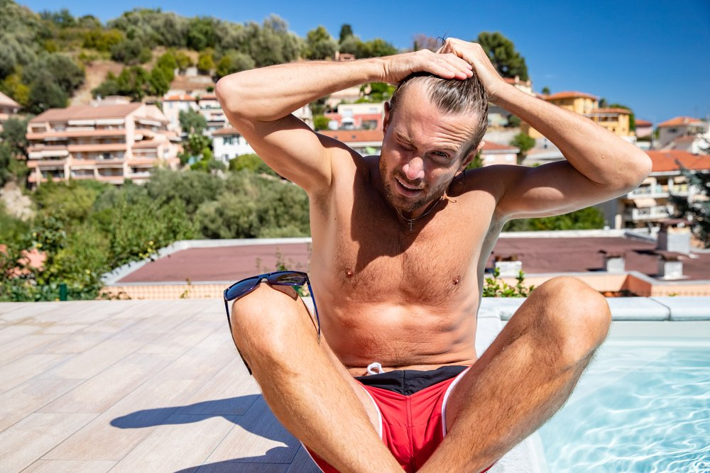 A topless man with a long hair sits near the pool as he ties his hair while sitting near a pool in swimming shorts | Photo: Shutterstock/Drozdin Vladimir