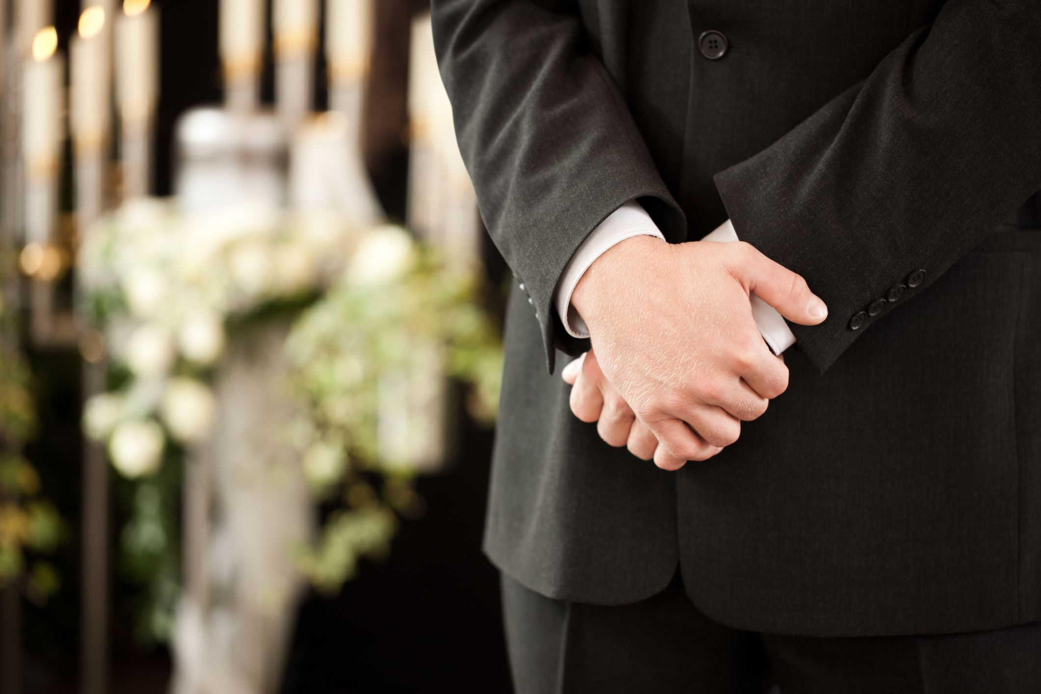A man at a funeral with his hands together.   Source: Getty Images
