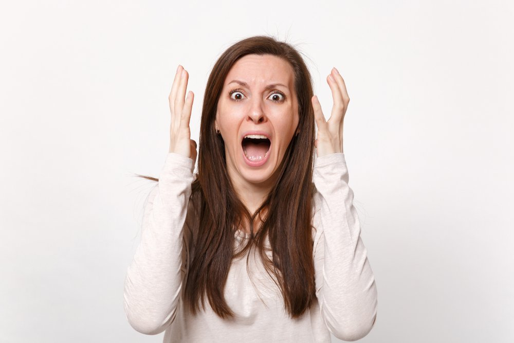 An angry woman screaming with her hands in the air. | Photo: Shutterstock.