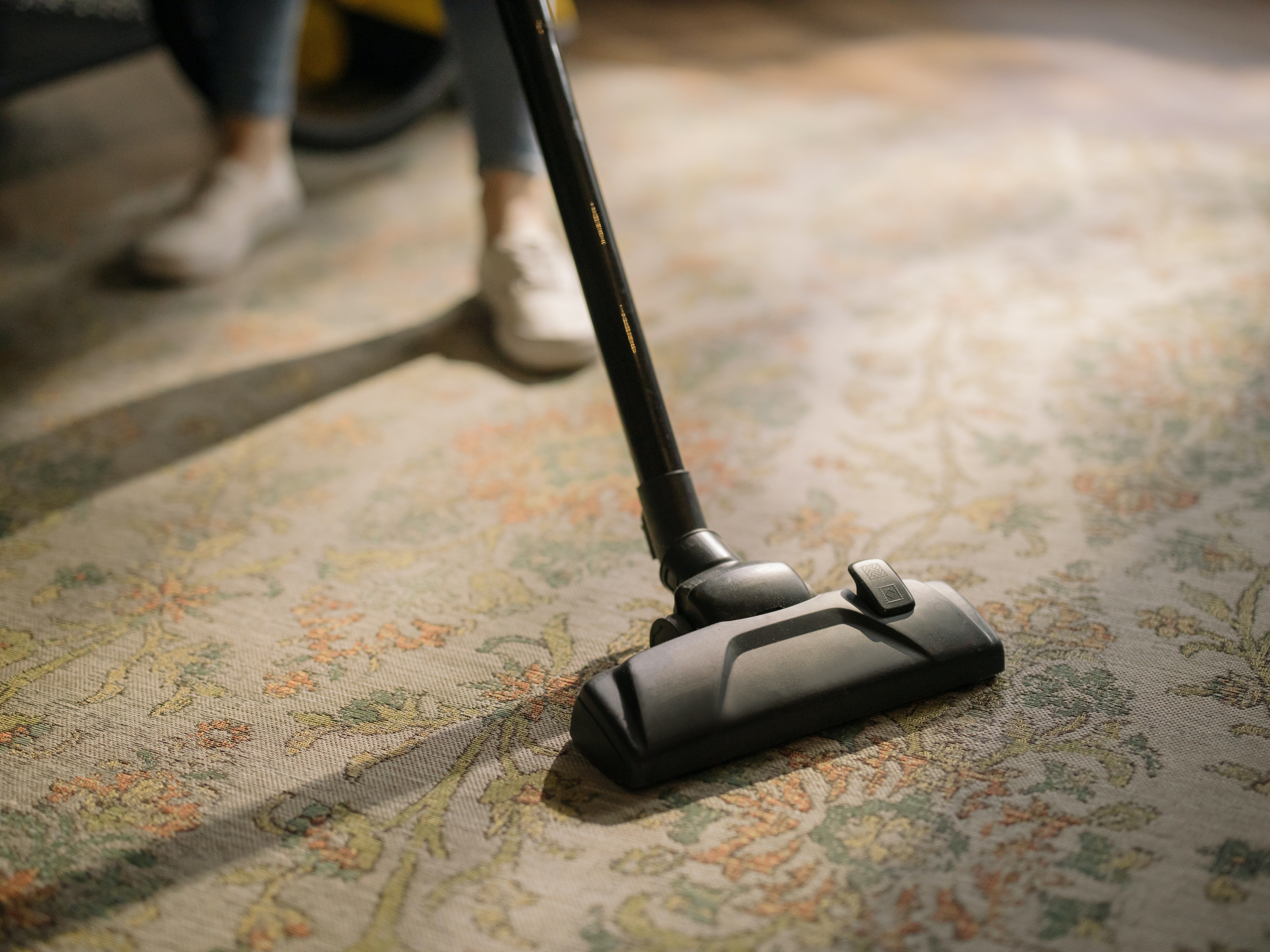 A vacuum cleaner on a carpet. | Photo: Pexels