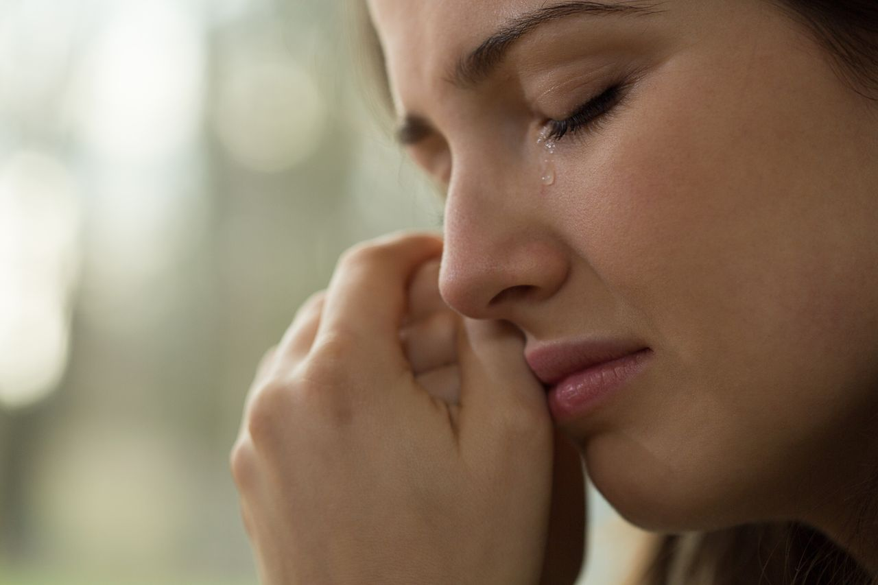 A woman cries while looking out a window. | Source: Shutterstock