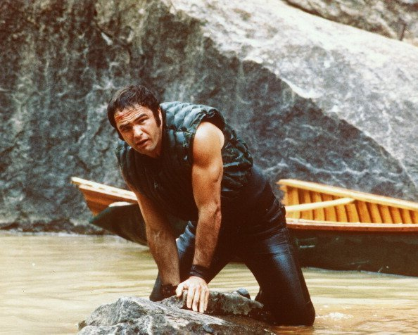 Burt Reynolds holding on to a rock in 1972 movie, Deliverance | Photo: Getty Images