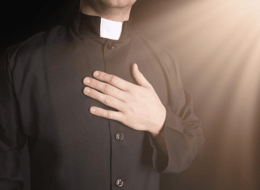 un homme d'église main sur le cœur | Photo : Shutterstock
