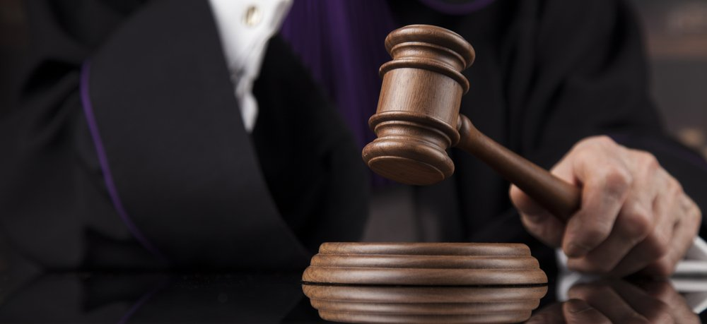 Un juge qui utilise son marteau en bois au Tribunal.   Shutterstock