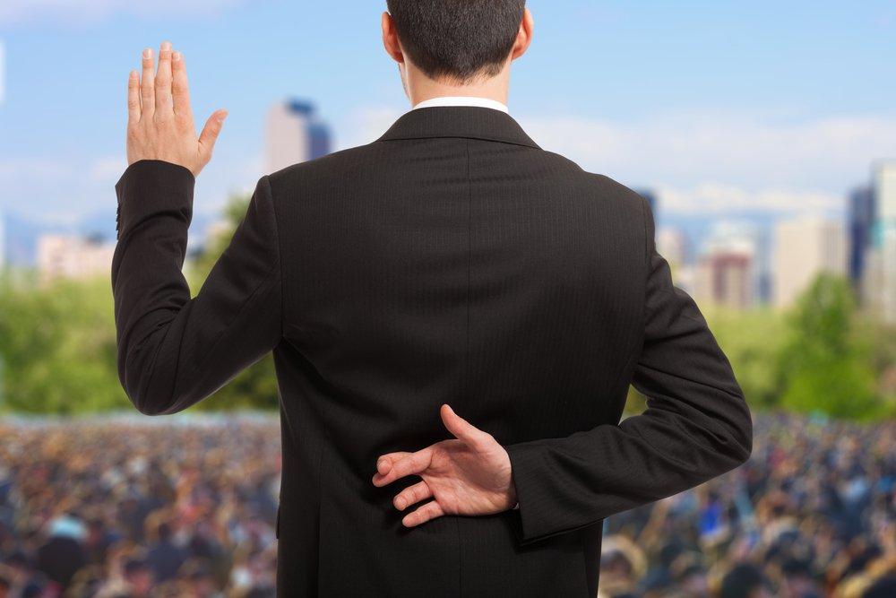 Político con los dedos cruzados detrás de la espalda. Fuente: Shutterstock